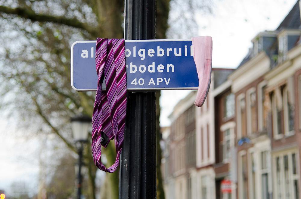Een roze balletschoen en een roze stropdas hangen over een alcoholsverbodbord bij de Vecht in Utrecht.<br /> <br /> A pink ballet shoe and a pink tie are draped round a sign which says that the use of alcohol is forbidden.