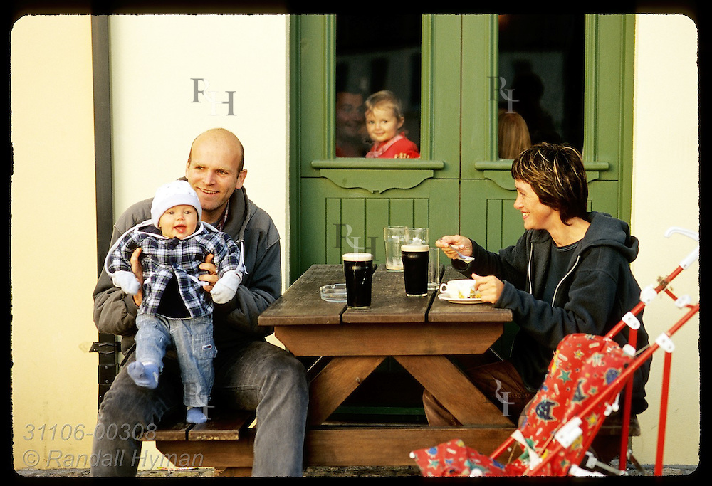 Parents and toddler eat dinner at table outside EJ Kings restaurant as child watches from window; Clifden, Connemara, Ireland