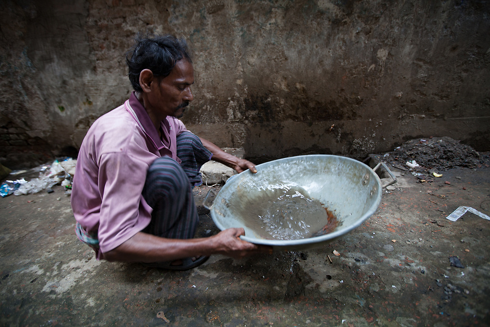 A man pans for gold in a drain on a street used by goldsmiths in Old Dkaha, Bangladesh