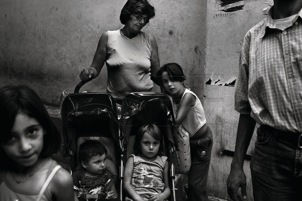 """Athens, Greece - Elny, 55, with her grandchildren, whose parents are both unemployed. Greek economical crisis started in 2008. The so-called Austerity measures imposed to the country by the """"Troika"""" (European Union, European Central Bank, and International Monetary Fund) to reduce its debt, were followed by a deep recession and the worsening of life conditions for millions of people. Unemployment rate grew from 8.5% in 2008 to 25% in 2012 (source: Hellenic Statistical Authority).They all rely on charity free food for living.Bruno Simões Castanheira"""