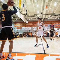 Gallup's Quinn Atazhoon (24) plays defense against Navajo Prep Thursday, Jan. 2 at the Gallup Invitational boys basketball tournament at Gallup High School.