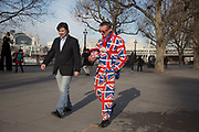 Street performer dressed in a Union Jack flag suit walking to his pitch on the riverfront walkway. The South Bank is a significant arts and entertainment district, and home to an endless list of activities for Londoners, visitors and tourists alike.