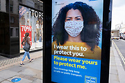 HM Government, Public Health England, NHS advertising boards advise people to take precaution of wearing a face mask under coronavirus lockdown on 1st July 2020 in London, England, United Kingdom. As the July deadline approaces and government will relax its lockdown rules further, the central London remains very quiet, while some non-essential shops are allowed to open with individual shops setting up social distancing systems.