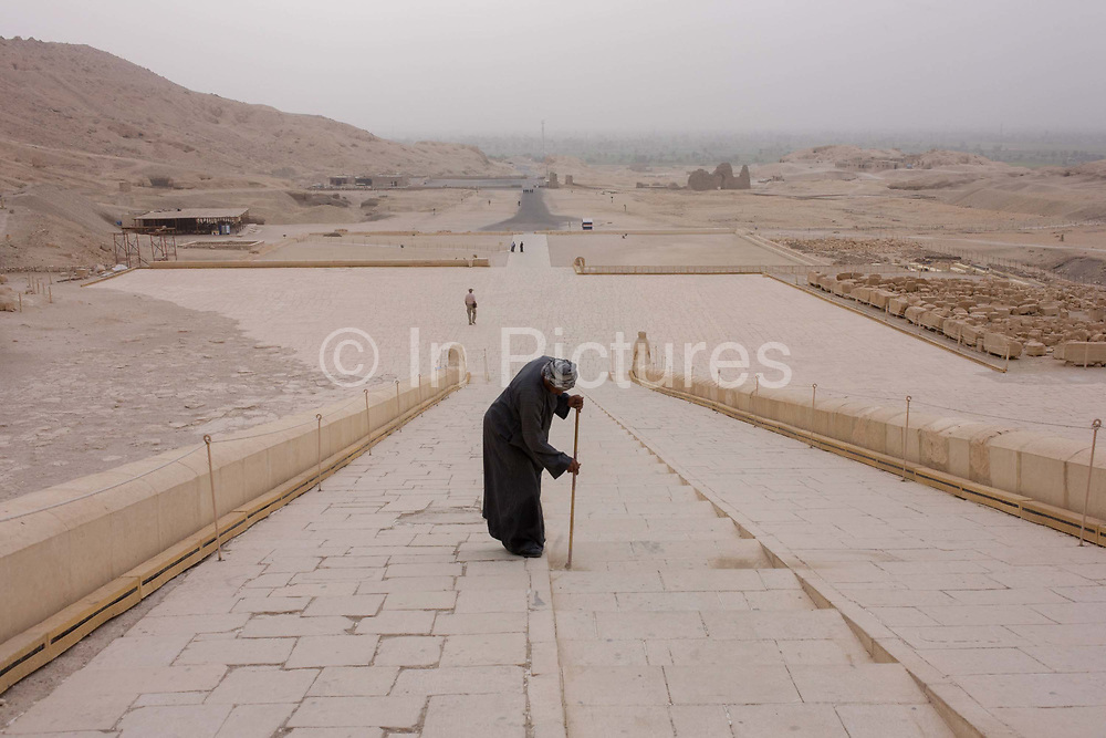 """A caretaker sweeps dusty steps at the otherwise deserted ancient Egyptian Temple of Hatshepsut near the Valley of the Kings, Luxor, Nile Valley, Egypt. According to the country's Ministry of Tourism, European visitors to Egypt is down by up to 80% in 2016 from the suspension of flights after the downing of the Russian airliner in Oct 2015. Euro-tourism accounts for 27% of the total flow and in total, tourism accounts for 11.3% of Egypt's GDP. The Mortuary Temple of Queen Hatshepsut, the Djeser-Djeseru, is located beneath cliffs at Deir el Bahari (""""the Northern Monastery""""). The mortuary temple is dedicated to the sun god Amon-Ra and is considered one of the """"incomparable monuments of ancient Egypt."""" The temple was the site of the massacre of 62 people, mostly tourists, by Islamists on 17 November 1997."""