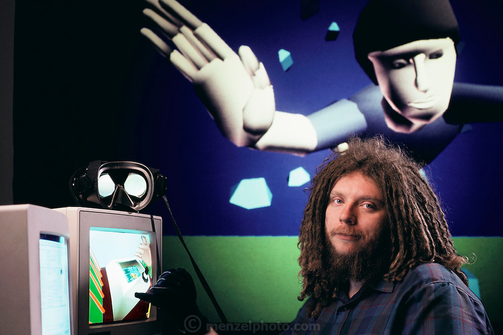 Virtual reality: Jaron Lanier, head of VPL Research of Redwood City, California, photographed surrounded by demonstration images of the virtual, non-real worlds that VPL have created. Fiber- optic sensors in the black rubber glove Lanier is wearing transmit a user's movements into the computer-generated virtual environment. A user's view of such a world is projected by the computer into 2 eye phones mounted on a headset (seen unworn at left, on top of the computer monitor). Model Released (1990)