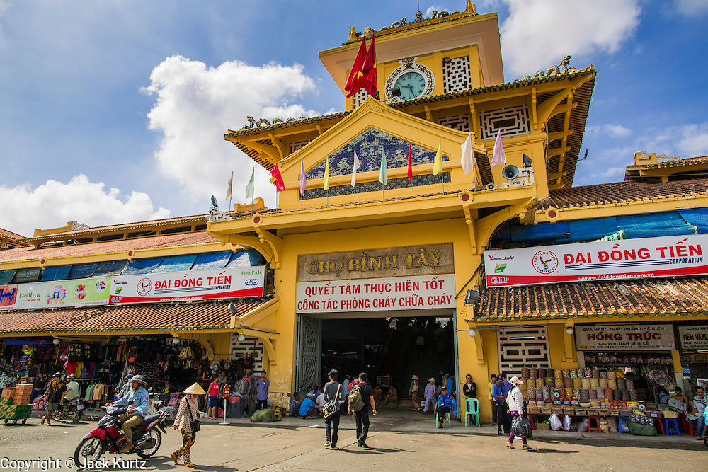 """12 APRIL 2012 - HO CHI MINH CITY, VIETNAM:  The main entrance to Binh Tay Market. Binh Tay market is the largest market in Ho Chi Minh City and is the central market of Cholon. Cholon is the Chinese-influenced section of Ho Chi Minh City (former Saigon). It is the largest """"Chinatown"""" in Vietnam. Cholon consists of the western half of District 5 as well as several adjoining neighborhoods in District 6. The Vietnamese name Cholon literally means """"big"""" (lon) """"market"""" (cho). Incorporated in 1879 as a city 11km from central Saigon. By the 1930s, it had expanded to the city limit of Saigon. On April 27, 1931, French colonial authorities merged the two cities to form Saigon-Cholon. In 1956, """"Cholon"""" was dropped from the name and the city became known as Saigon. During the Vietnam War (called the American War by the Vietnamese), soldiers and deserters from the United States Army maintained a thriving black market in Cholon, trading in various American and especially U.S Army-issue items.         PHOTO BY JACK KURTZ"""