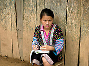 Hmong girl doing her school homework outside the dormitory where she lives during term time to go to lower secondary school in the Tai Lue village of Ban Hathin, Phongsaly province, Lao PDR. The remote and roadless village of Ban Hathin is situated along the Nam Ou river (a tributary of the Mekong) and  will be relocated due to the construction of the Nam Ou Cascade Hydropower Project Dam 7. The Nam Ou river connects small riverside villages and provides the rural population with food for fishing. But this river and others like it, that are the lifeline of rural communities and local economies are being blocked, diverted and decimated by dams. The Lao government hopes to transform the country into 'the battery of Southeast Asia' by exporting the power to Thailand and Vietnam.
