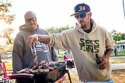 Roman Garcia and John Lincoln, right, grill up some sausages and chicken as Fast Lane Band performs during the Milpitas Summer Concert Series at Murphy Park in Milpitas, California, on July 14, 2015. (Stan Olszewski/SOSKIphoto)
