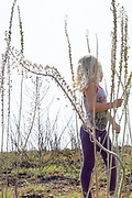 Young girl of 4 plays in a field of flowering Sea Squill, (Drimia maritima). Photographed in Israel, autumn October