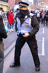 """© Licensed to London News Pictures. 20/03/2021. Manchester, UK. A police officer picks up a police radio after someone pulled it from a police officer's uniform and ran away with it before throwing it in the road . A """" Kill the Bill """" and Reclaim the Streets protest demonstration is held in St Peter's Square in Manchester City Centre in opposition to the Police, Crime, Sentencing and Courts Bill 2021 that is currently before Parliament and after the death of Sarah Everard in London . Photo credit: Joel Goodman/LNP"""