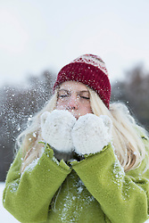Teenage girl blowing snow, Bavaria, Germany