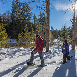 A woman and her daughter snowshoe next to the Hudson River near its source in New York's Adirondack Mountains. Upper Works Trail, Tahawus Tract, Newcomb, New York.