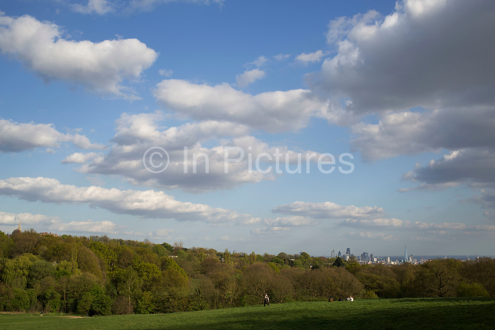 """View from high across Hampstead Heath towards the City of London. Hampstead Heath (locally known as """"the Heath"""") is a large, ancient London park, covering 320 hectares (790acres). This grassy public space is one of the highest points in London, running from Hampstead to Highgate. The Heath is rambling and hilly, embracing ponds, recent and ancient woodlands."""