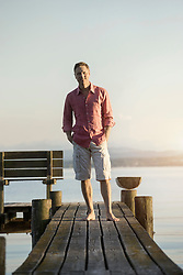 Mature man standing on wooden pier with hands on pockets, Bavaria, Germany