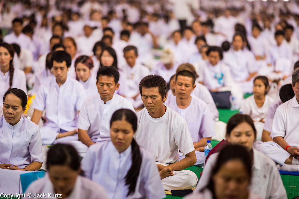 "14 FEBRUARY 2014 - KHLONG LUANG, PATHUM THANI, THAILAND: People meditate during afternoon meditation on Makha Bucha Day at Wat Phra Dhammakaya.  The aims of Makha Bucha Day are: not to commit any kind of sins, do only good and purify one's mind. It is a public holiday in Cambodia, Laos, Myanmar and Thailand. Many people go to the temple to perform merit-making activities on Makha Bucha Day. The day marks four important events in Buddhism, which happened nine months after the Enlightenment of the Buddha in northern India; 1,250 disciples came to see the Buddha that evening without being summoned, all of them were Arhantas, Enlightened Ones, and all were ordained by the Buddha himself. The Buddha gave those Arhantas the principles of Buddhism, called ""The ovadhapatimokha"". Those principles are:  1) To cease from all evil, 2) To do what is good, 3) To cleanse one's mind. The Buddha delivered an important sermon on that day which laid down the principles of the Buddhist teachings. In Thailand, this teaching has been dubbed the ""Heart of Buddhism."" Wat Phra Dhammakaya is the center of the Dhammakaya Movement, a Buddhist sect founded in the 1970s and led by Phra Dhammachayo.    PHOTO BY JACK KURTZ"