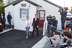© Licensed to London News Pictures . 07/05/2015 . Doncaster , UK . Labour leader Ed Miliband and his wife Justine Thornton leave Sutton Village Hall polling station in Doncaster North with Labour party staff pointing to a white chip on the ground where the two should stop for a photograph , after voting at the general election . Photo credit : Joel Goodman/LNP
