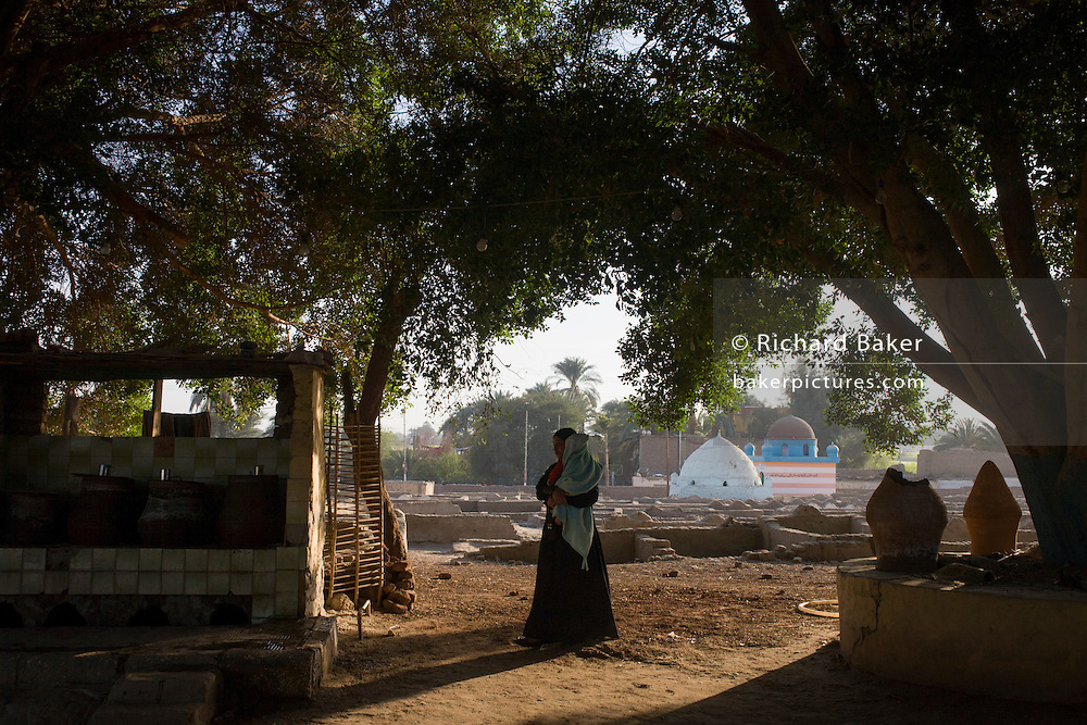 A local woman walks through evening sunlight in a local cemetery in the village of Qum (Koom), on the West Bank of Luxor, Nile Valley, Egypt.