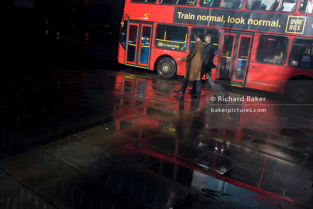 City businessmen pass-by red London bus in strong sunshine after recent heavy rain showers.
