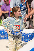 A young girl covered in sticky grits smiles during the World Grits Festival rolling in the grits contest April 12, 2014 in St. George, South Carolina. Contestants have to roll in a vat of grits and the one with the most grits sticking to their body wins. Grits are a tradition Southern dish of thick maize-based porridge made from dried corn hominy.