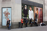 Employees from high street fashion retailer Topshop smoke under ad posters at the rear of their store.