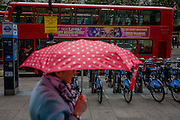 The Australian character Dame Edna Everage looks over the street from a bus ad to a woman carrying an umbrella during autumnal London showers.