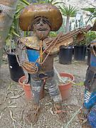 metal garden figurine displayed between plants in garden center