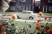 A Ford Anglia is parked in an empty road and homegrown beds of dahlias grow in the front garden of a council house in the early 1960s. Looking through the clean window we see net curtains (drapes) and in the foreground are the flowers showing a prospering post-war era. The car is the only one parked in the road at a time when car ownership was still to become popular among the working and middle-classes is estates like this. The colours are brilliantly reproduced and recorded by Kodachrome film by an amateur photographer in 1963. The picture shows us a memory of nostalgia in an era from the last century.