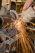 a metal garden tool being sharpened on a grinder sends sparks out