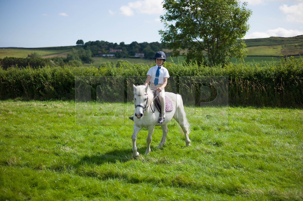 © Licensed to London News Pictures.12/08/15<br /> Danby, UK. <br /> <br /> A young girl exercises her horse ahead of a jumping event during the 155th Danby Agricultural Show in the Esk Valley in North Yorkshire. <br /> <br /> The popular agricultural show attracts competitors and visitors from all over the surrounding area to this annual showcase of country life. <br /> <br /> Photo credit : Ian Forsyth/LNP