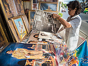 01 DECEMBER 2016 - BANGKOK, THAILAND: A shopkeeper sets out photos of the Thai royal family, including Crown Prince Vajiralongkorn (foreground), who will soon be the new King. Thailand's parliamentary body, the National Legislative Assembly, invited HRH Crown Prince Maha Vajiralongkorn to be king following the death of the Crown Prince's father, Bhumibol Adulyadej, the Late King of Thailand. The invitation marked the formal beginning of the process of naming the new King, although Crown Prince Vajiralongkorn was the heir apparent and Bhumibol's appointed successor. Shops that sell royal paraphernalia are now selling new portraits of  Crown Prince Vajiralongkorn which will be displayed alongside portraits of his late father. King Bhumipol died on Oct 13.      PHOTO BY JACK KURTZ
