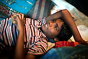 Ravi, 11, Poonam's older brother, is relaxing on a bed, while eating biscuits inside his family's newly built home in Oriya Basti, one of the water-affected colonies in Bhopal, Madhya Pradesh, India, near the abandoned Union Carbide (now DOW Chemical) industrial complex.