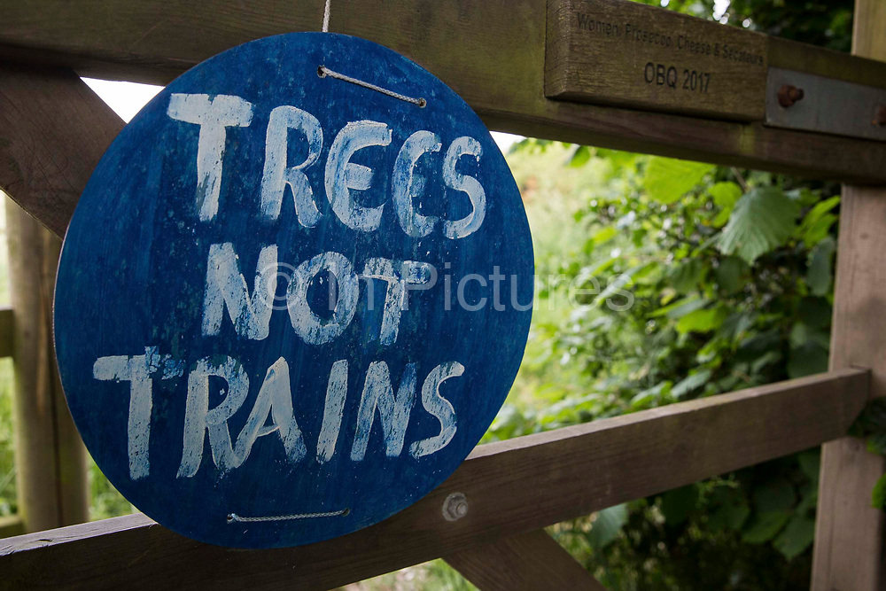 A sign reading Trees Not Trains is pictured close to ancient woodland at Jones Hill Wood in Buckinghamshire where works for the HS2 high-speed rail link continue on 16th June 2021 in Wendover, United Kingdom. A large section of the ancient woodland, which contained resting places and/or breeding sites for pipistrelle, barbastelle, noctule, brown long-eared and natterer's bats, has now been entirely cleared of trees and vegetation by contractors working on behalf of HS2 Ltd.