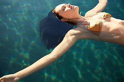 Portrait of young woman floating in crystal clear water