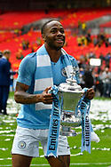 Raheem Sterling (7) of Manchester City holds up the FA Cup at full time during the The FA Cup Final match between Manchester City and Watford at Wembley Stadium, London, England on 18 May 2019.
