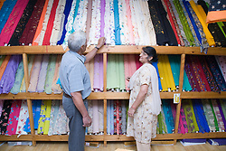 Older woman out shopping for dress fabric,