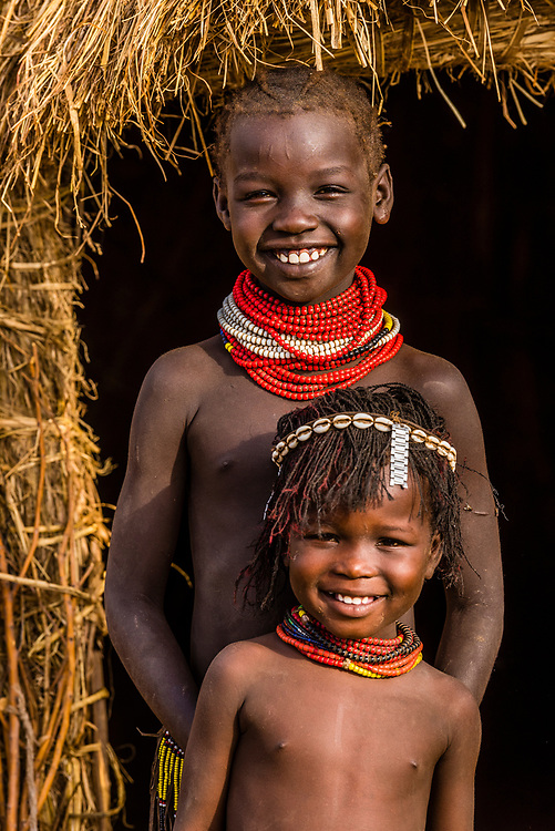 Nyangatom tribe girls in front of their famiy's hut, Omo Valley, Ethiopia.