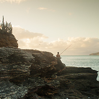 A man fishes off Tartaruga beach, Búzios, Brazil. <br /> Pescador, Búzios Brasil