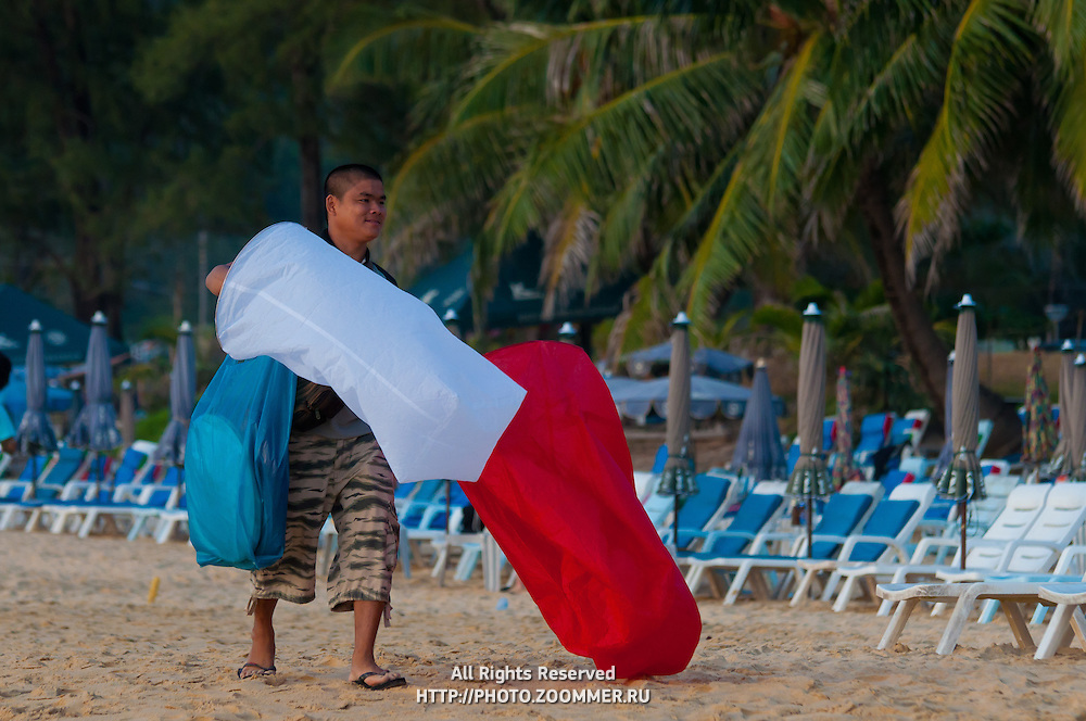 Thai boy selling sky lanterns on Karon beach, Phuket, Thailand