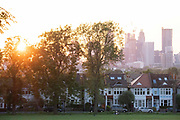 With the tall towers at Nine Elms in the distance, a sun sets below a line of homes and ash trees in Ruskin Park, a public green space in Lambeth, south London, on 12th June 2021, in London, England.