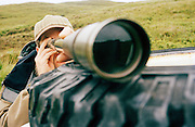 A hunter who is deer stalking looking through a telescope in Knoydart in the Scottish highlands, UK