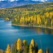 Vertical scenic view of Holland Lake, Swan Valley, Swan Mountain Range and Mission Mountains (aka the American Alps) from Holland Falls National Recreation Trail.  Autumn color of Ponderous Pine, Red Fir, and Western Larch frame the lake.  Western Montana, USA. Published in Landscape Photography magazine, Issue 82 / Dec. 2017.