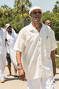 Public radio host of the Roots Musik Karamu show, Osei Chandler, leads descendants of enslaved Africans brought to Charleston in the Middle Passage in a procession during a remembrance ceremony at Fort Moutrie National Monument June 10, 2017 in Sullivan's Island, South Carolina. The Middle Passage refers to the triangular trade in which millions of Africans were shipped to the New World as part of the Atlantic slave trade. An estimated 15% of the Africans died at sea and considerably more in the process of capturing and transporting. The total number of African deaths directly attributable to the Middle Passage voyage is estimated at up to two million African deaths.