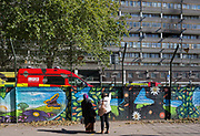 Local estate residents look up at smoke damage aftermath on the exterior of a flat fire in one of the two Wendover blocks on Alsace Road in the Aylesbury Estate, Southwark SE17, on 24th September 2018, in London, England. Part of a split level flat on the fourth and fifth floor of the 15-storey block was damaged. One woman and two children left the property before the Brigade arrived. They were treated at the scene for smoke inhalation by London Ambulance Service crews and taken too hospital. Another man was also treated at the scene for smoke inhalation.
