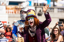 © Licensed to London News Pictures. 18/07/2021. LONDON, UK. An actor dressed as The Mad Hatter (as a white rook) at Chess Fest in Trafalgar Square.  The event celebrates the game of chess and visitors can learn the game, play chess or challenge a Grandmaster.  Also, to celebrate the 150th anniversary of Lewis Carroll's Alice Through the Looking Glass book which featured the game of the chess, 32 actors dressed as Alice Through the Looking Glass characters stand on a giant chessboard replaying a game based on the book.  Photo credit: Stephen Chung/LNP