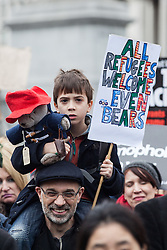 © Licensed to London News Pictures. 19/03/2016. London, UK. A young boy sits on his father's shoulders with a banner and Paddington Bear toy. Thousands march through central London on UN anti-racism day to demand that the British government accept a greater share of refugees seeking asylum in Europe. Photo credit : Rob Pinney/LNP