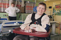 Young boy with Cerebral Palsy sitting in a wheelchair on Children's ward in hospital; smiling and playing with toy car,