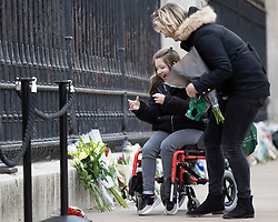 © Licensed to London News Pictures.10/04/2021. London, UK. A young girl in a wheelchair places flowers in front of Buckingham Palace. Yesterday Buckingham Palace announced that Prince Philip The Duke of Edinburgh passed away in the morning at Windsor Castle . Photo credit: George Cracknell Wright/LNP