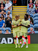 Football - 2021 / 2022 Premier League - Burnley vs. Arsenal<br /> <br /> Martin Odegaard of Arsenal celebrates  with Bukayo Saka after he curls a free kick around the Burnley wall to put his team 1-0 ahead in the first half, at Turf Moor.<br /> <br /> <br /> COLORSPORT/ALAN MARTIN
