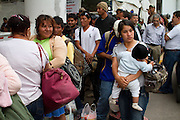 """Migrant women line outside the migrants temporary shelter in Tultitlán, Estado de México to be transported to Huehuetoca on August 3rd, 2012.  Tultitlán local authorithies ordered to dismantle the temporary shelter that was placed under a bridge in Tultitlán after shelter  """"San Juan Diego Cuauhtlatoatzin"""" in Lecheria, was closed on July 9th, 2012. (Photo: Prometeo Lucero)"""
