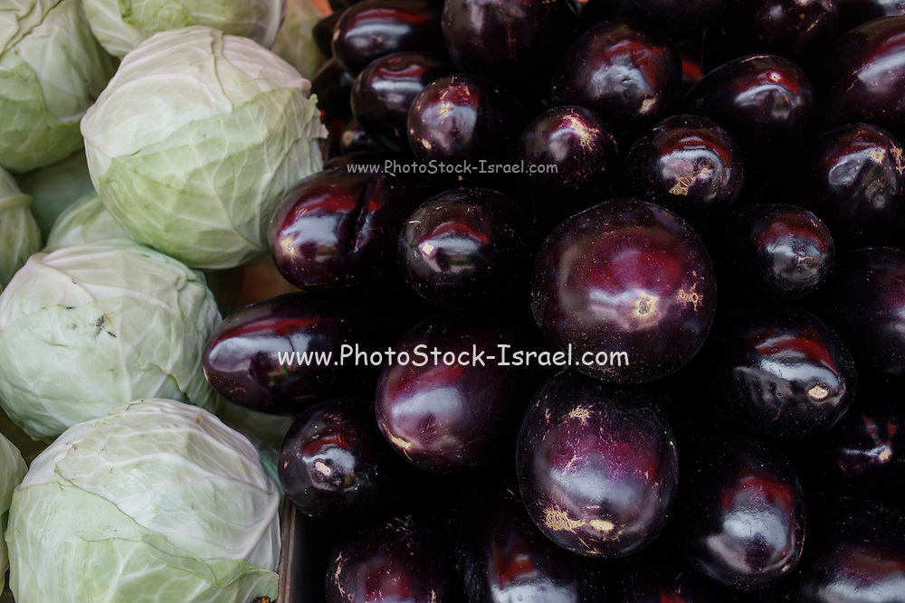 a stack of eggplants on a stall